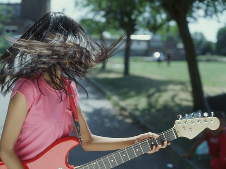 all under 18: Teenager tossing hair while playing guitar