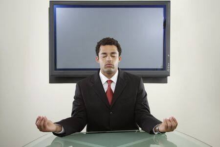 Businessman meditating in front of monitor