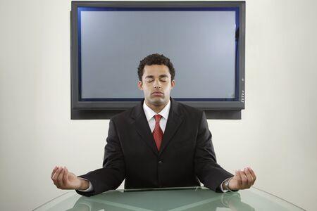 irish ethnicity: Businessman meditating in front of monitor