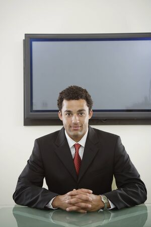 irish ethnicity: Businessman seated in front of flat screen LANG_EVOIMAGES