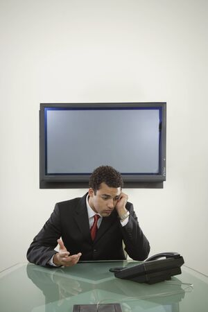 Young businessman staring at his telephone Stock Photo