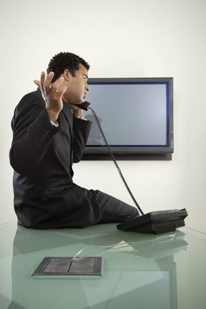 irish ethnicity: Young businessman talking on telephone