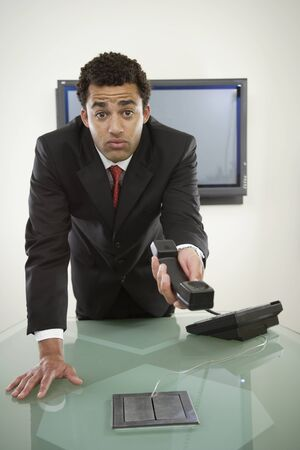 Perplexed businessman holding telephone Stock Photo - 16072067