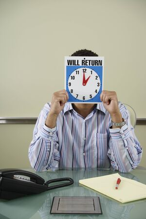 Office worker holding clock in front of face Stock Photo - 16072074