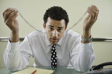 Businessman staring at paperclip chain