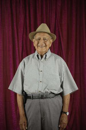 latino man: Elderly man standing and smiling