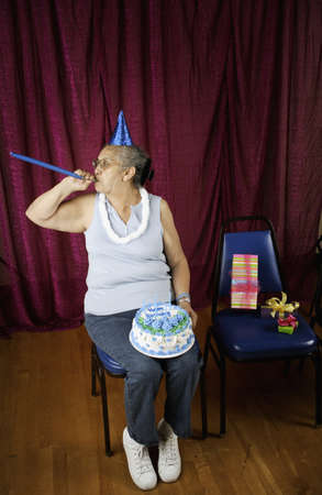 noisemaker: Woman with party favors and birthday cake