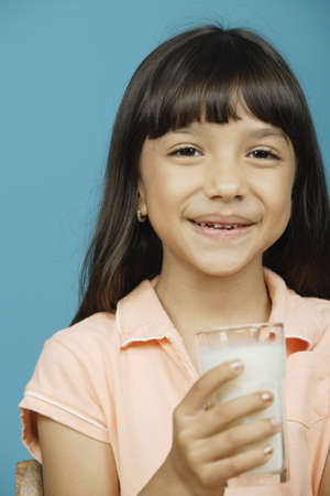 all under 18: Young girl holding glass of milk