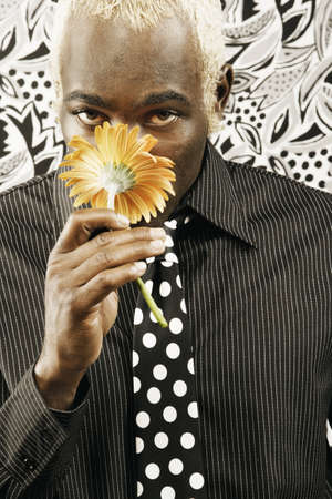 hither: Young man smelling yellow flower