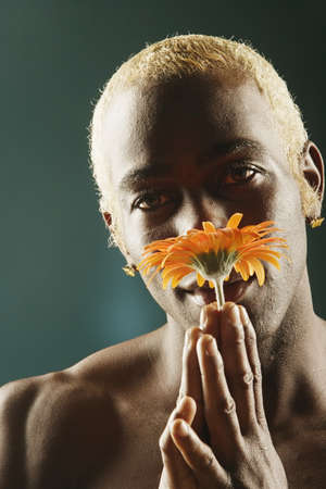 come hither: Young man smelling orange flower