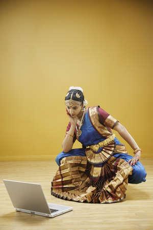 you've got mail: Exotic woman contemplating laptop computer LANG_EVOIMAGES
