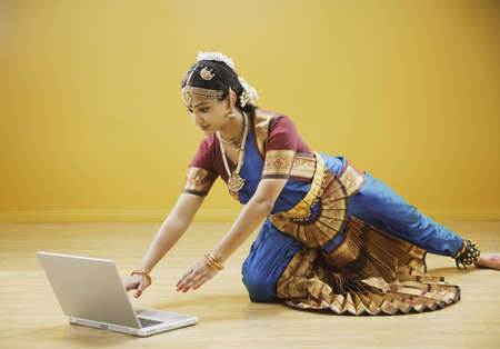 you've got mail: Exotic woman reaching for laptop computer