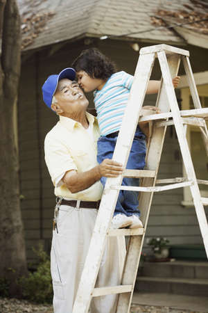 some under 18: Little girl giving grandpa a kiss while standing on a ladder