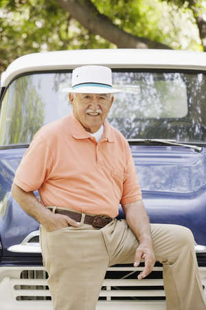leaning on the truck: Portrait of elderly man leaning on old pickup truck