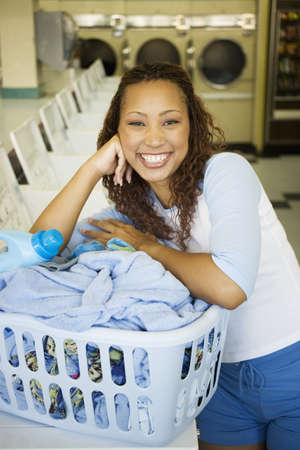 laundromat: Portrait of woman with basket of  clothes in laundromat LANG_EVOIMAGES