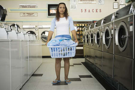 laundromat: Full view of woman with basket of  clothes in laundromat