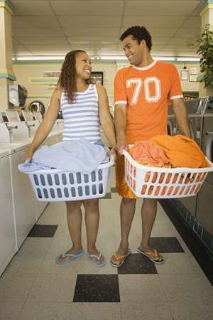 laundromat: Couple carrying baskets of  clothes in laundromat