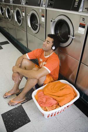 laundromat: Man sitting on floor listening to music in laundromat