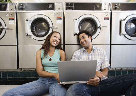 Couple looking at each other while sitting on the floor with laptop in laundromat Stock Photo - 16072147