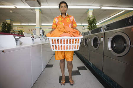 laundromat: Man standing in laundromat with laundry