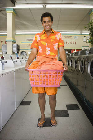 laundromat: Portrait of man standing in laundromat with laundry LANG_EVOIMAGES