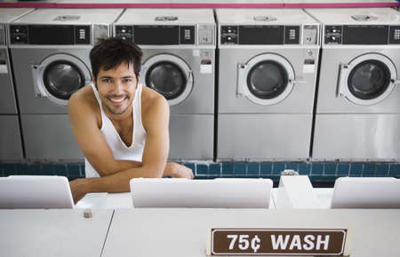 above 25: Portrait of man in tank top at laundromat LANG_EVOIMAGES