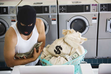 money laundering: Man in ski mask with bags of money at laundromat