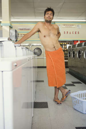 laundromat: Man wrapped in towel standing in laundromat