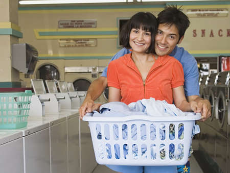 Portrait of couple with laundry hugging at laundromat Stock Photo - 16072155