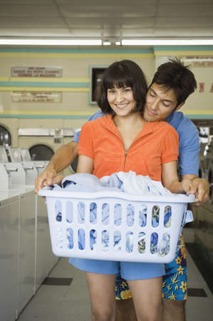 Couple with laundry hugging at laundromat Stock Photo - 16072156