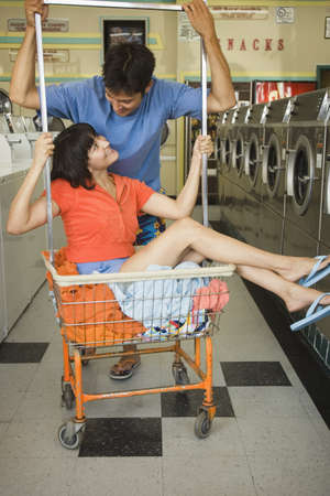 Couple with laundry cart at laundromat Stock Photo - 16072157