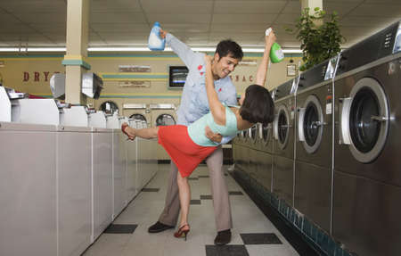 Couple dancing with soap in laundromat Stock Photo - 16072159
