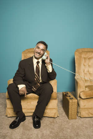 Portrait of businessman in chair talking on phone Stock Photo - 16072163