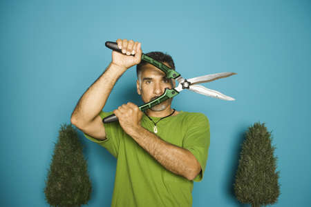hedge clippers: Portrait of man holding hedge clippers in front of face LANG_EVOIMAGES