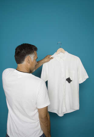 above 30: Rear view of man holding ink stained shirt