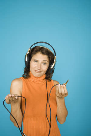 unplugged: Portrait of woman holding end of  unplugged headset