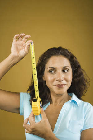 Woman looking sideways holding tape measure Stock Photo - 16072178