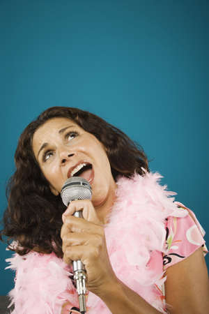 Woman wearing feather boa singing into microphone Stock Photo - 16072180
