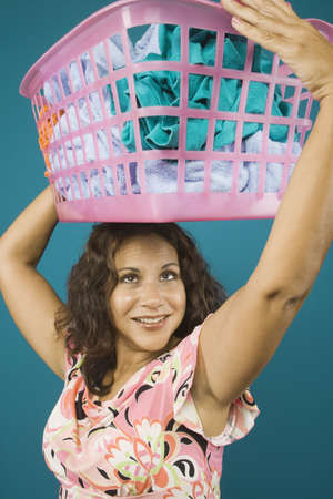 Woman balancing basket of dirty clothes on head Stock Photo - 16072182
