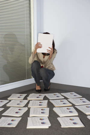Businesswoman hiding face with papers Stock Photo - 16072193