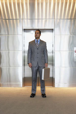 Young businessman standing outside of elevator Stock Photo