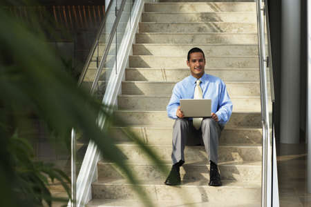 Businessman with laptop sitting on step Stock Photo - 16072197