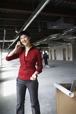 Woman on mobile phone at construction site Stock Photo - 16072199