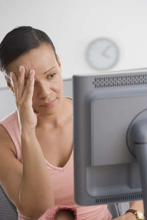 above 30: Frustrated woman looking at computer with hand on face