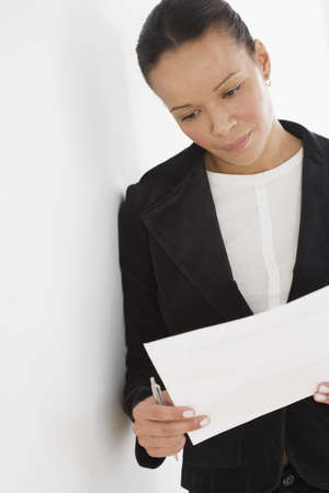 above 30: Businesswoman reading paperwork while leaning against wall