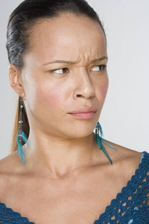 Woman frowning while looking off to side Фото со стока
