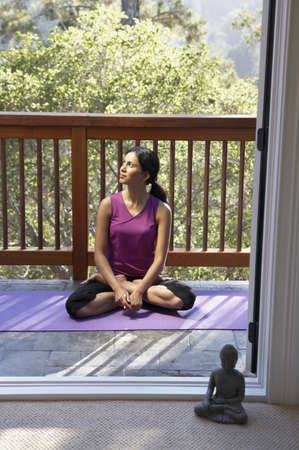 mid afternoon: Woman looking sideways while in meditation position