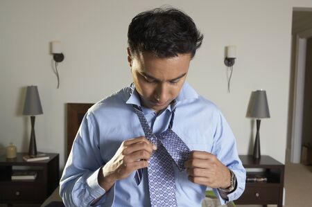 above 25: Businessman tying tie