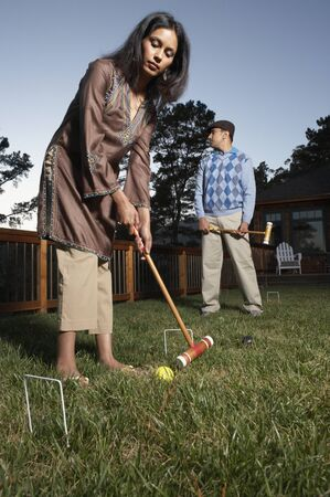 mid afternoon: Couple playing croquet in yard