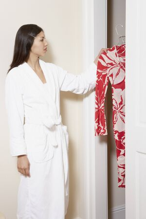 Side view of woman in robe looking through closet
